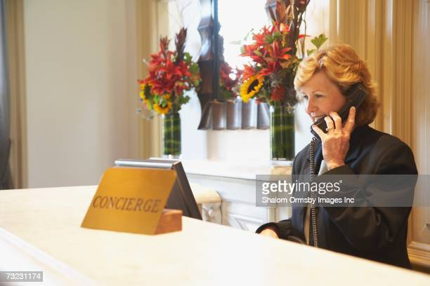 Woman using telephone behind hotel reception desk