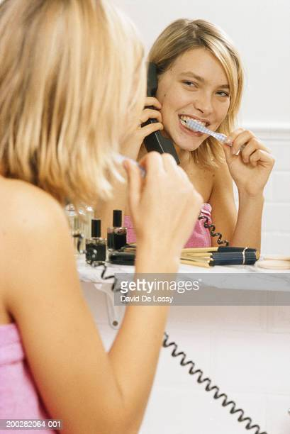Woman using telephone, brushing teeth