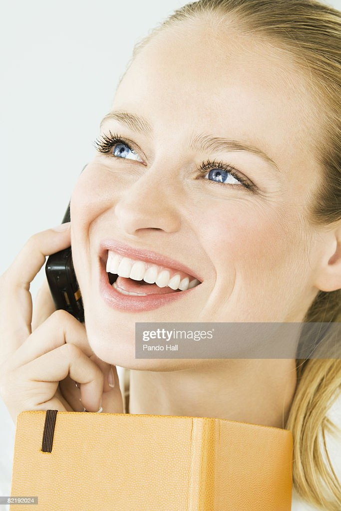 Woman using telephone, holding book, laughing : Stock Photo