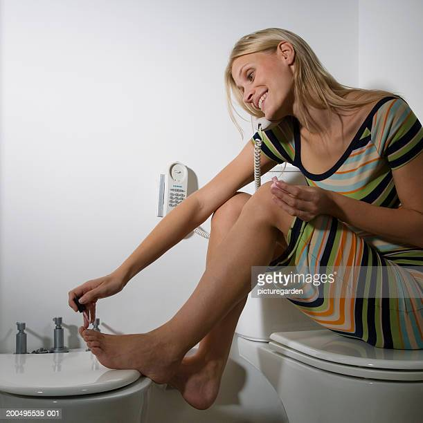 Woman using telephone in bathroom whilst painting nails