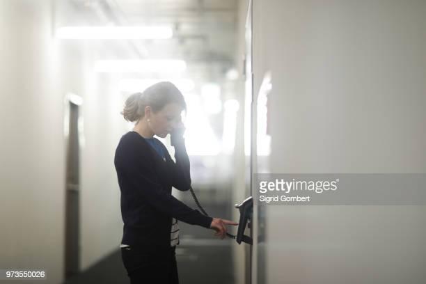 woman using telephone in office - sigrid gombert fotografías e imágenes de stock
