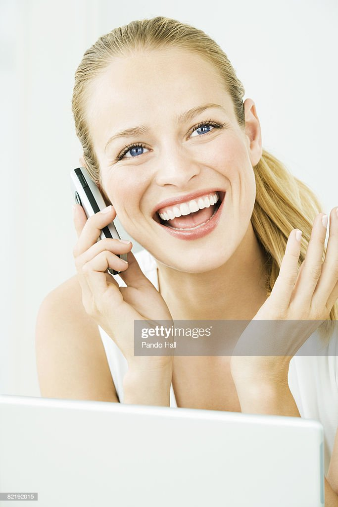 Woman using telephone, laptop in front : Stock Photo