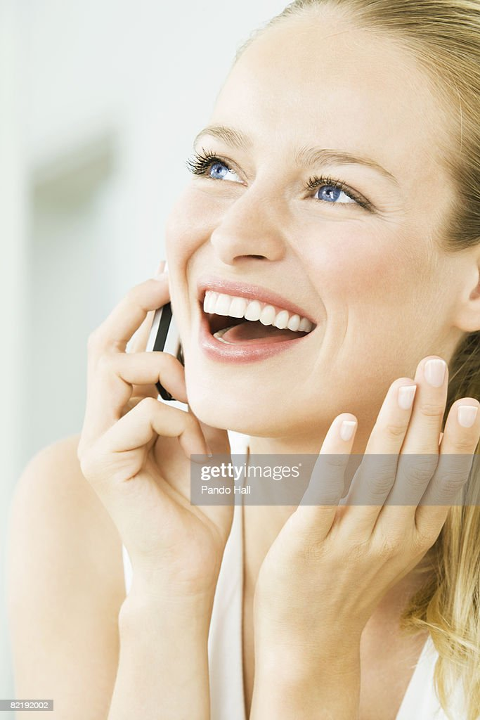 Woman using telephone, laughing, portrait : Stock Photo
