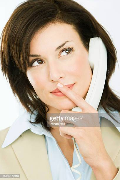 Woman using telephone, looking up, close-up