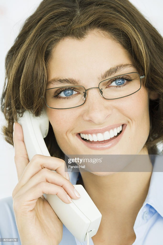 Woman using telephone, smiling : Stock Photo
