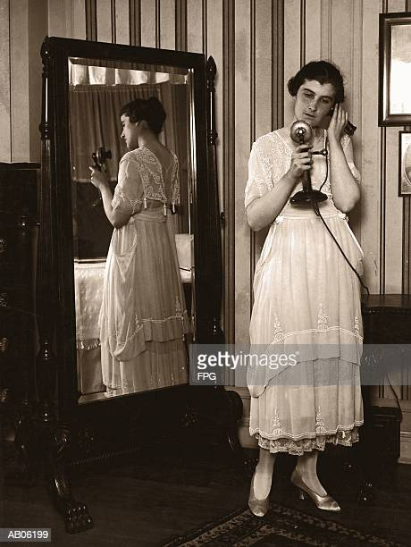 woman using telephone, standing by mirror (b&w sepia tone) - full length mirror stock photos and pictures