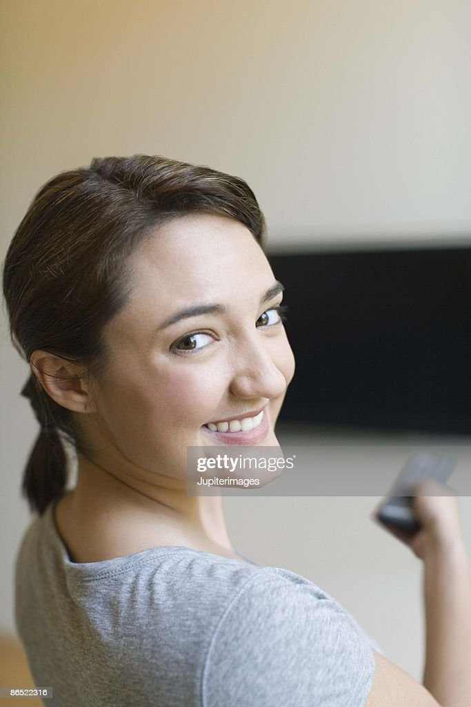 Woman using television remote control : Stock Photo