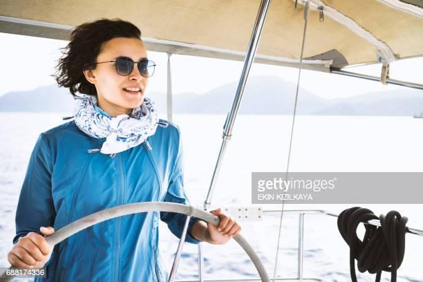 Woman using the boat's wheel, sailing