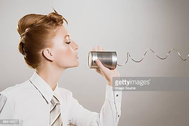 Woman using tin can phone