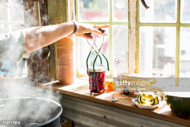 Woman using tongs to remove beetroot preserves jar from steaming saucepan