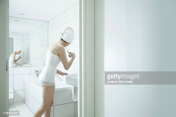woman using toothbrush standing at a bathroom sink