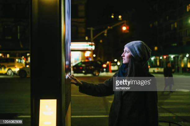woman using touch screen city display - kiosk stock pictures, royalty-free photos & images