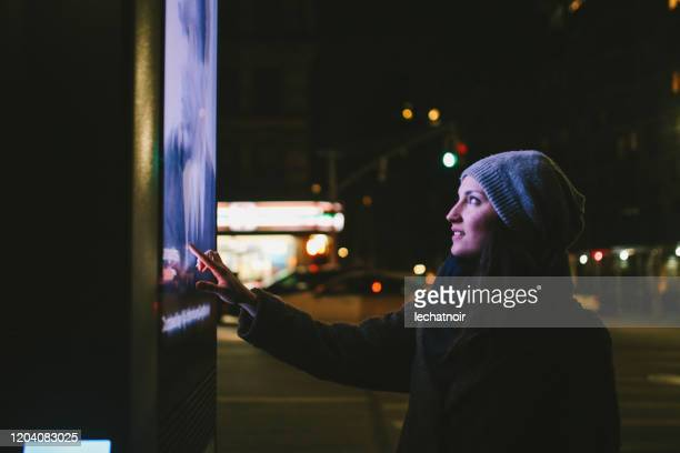 frau mit touchscreen-stadtdisplay - one night stand stock-fotos und bilder