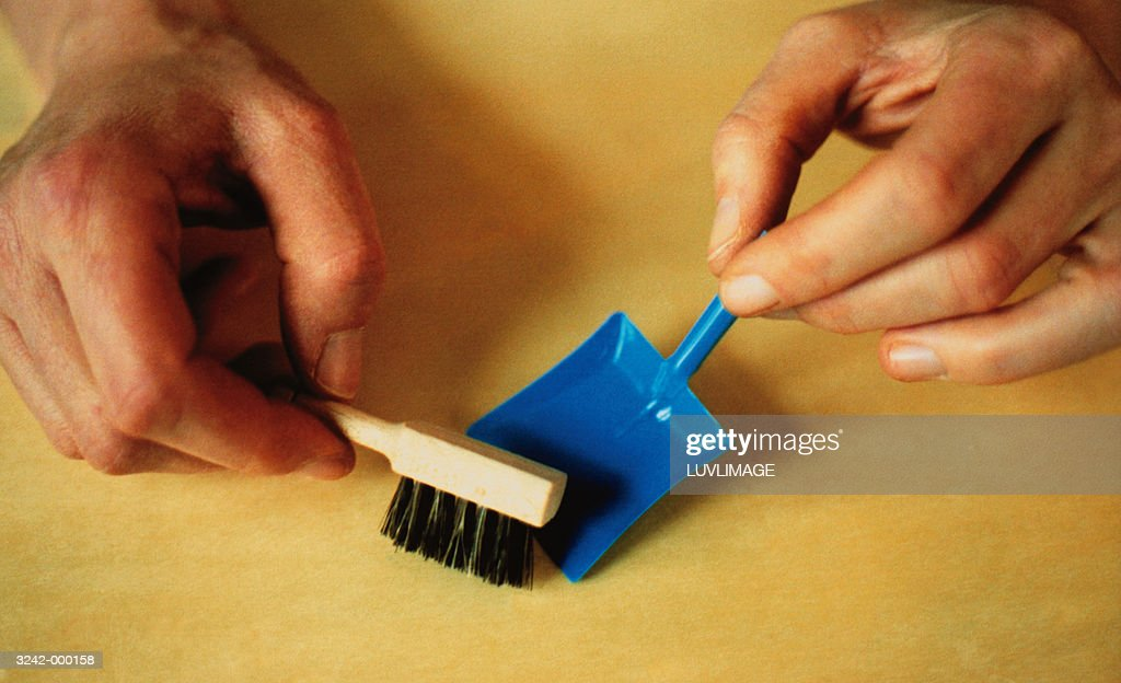 Woman using toy dust pan and brush, close-up : Stock Photo