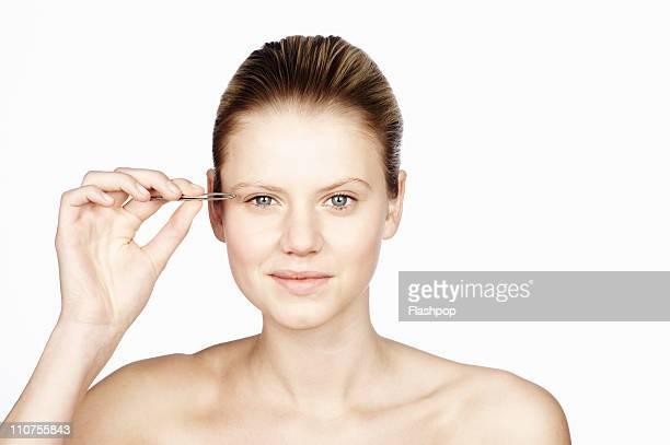 Woman using tweezers to pluck her eyebrows
