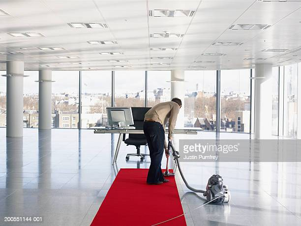 Woman using vacuum cleaner in office, rear view