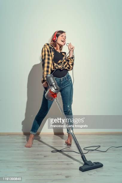 woman using vacuum cleaner - gender role fotografías e imágenes de stock