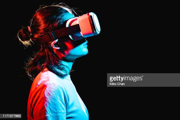 woman using virtual reality headset at night - simulatore di realtà virtuale foto e immagini stock