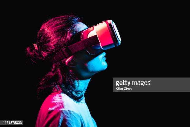 woman using virtual reality headset at night - interaktivität stock-fotos und bilder