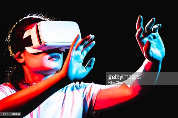 woman using virtual reality headset at night - 仮想空間の視点 ストックフォトと画像