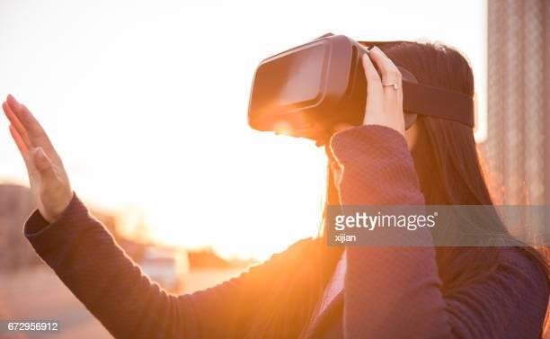 Woman using virtual reality headset at sunset
