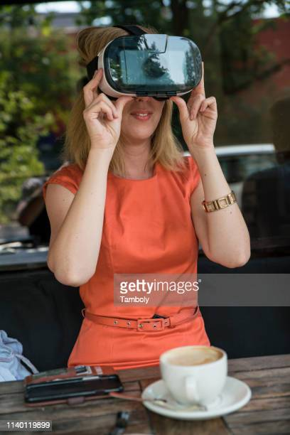 woman using virtual reality headset in cafe - orange dress stock pictures, royalty-free photos & images