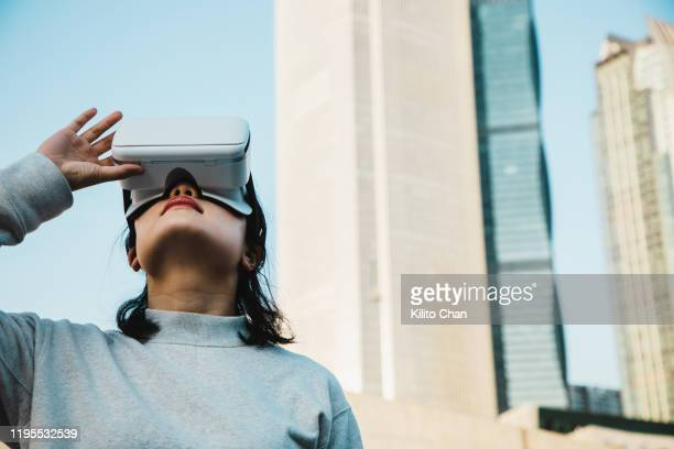 woman using virtual reality headset in the cityscape - 仮想空間の視点 ストックフォトと画像