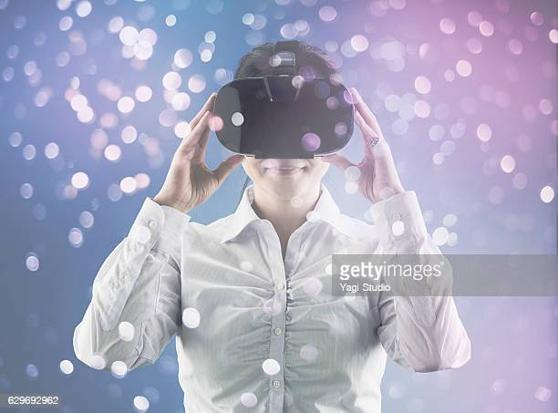 woman using virtual reality headset - head mounted display stock photos and pictures