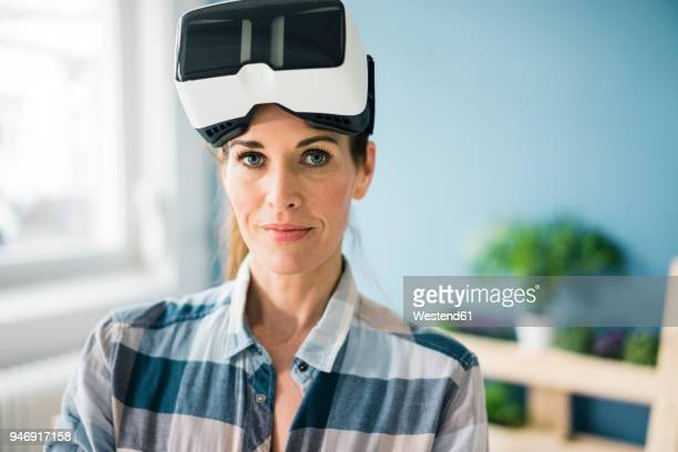 Woman using VR glasses, renovating her new home