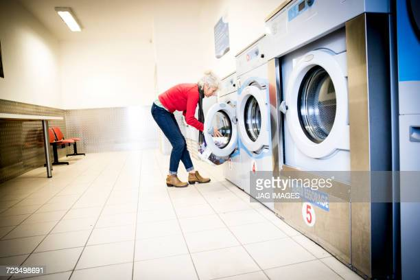 woman using washing machine in laundrette - older woman bending over stock pictures, royalty-free photos & images