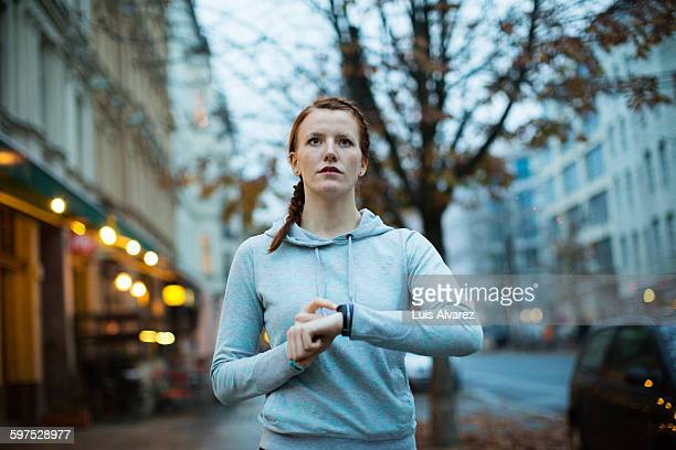 Woman using watch before exercising on sidewalk