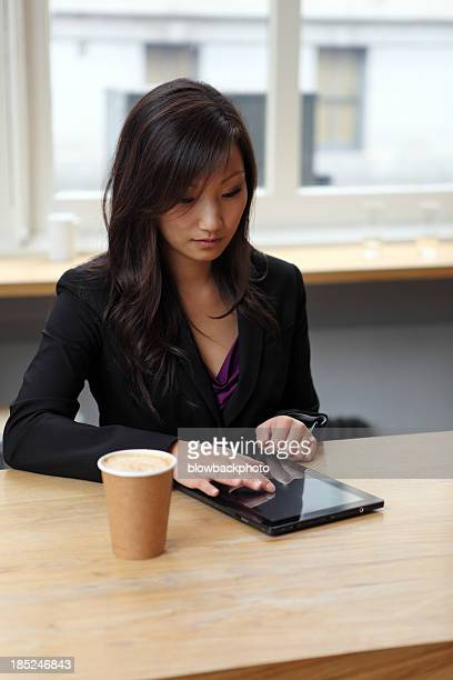 Woman Using Web Tablet in a Coffee Shop