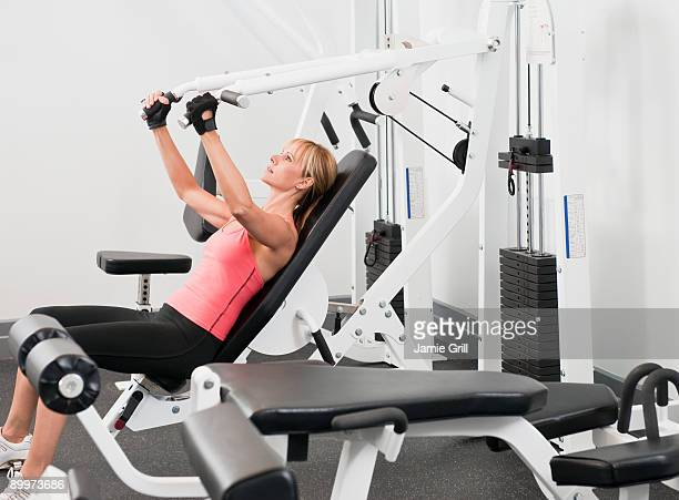 Woman using weight lifting machine at gym