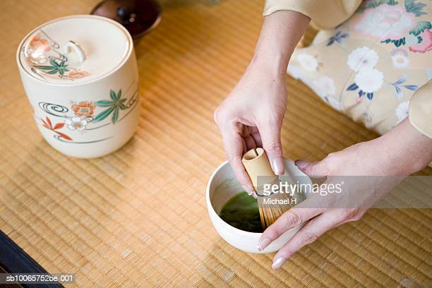 Woman using whisk to mix green tea, close up of hands