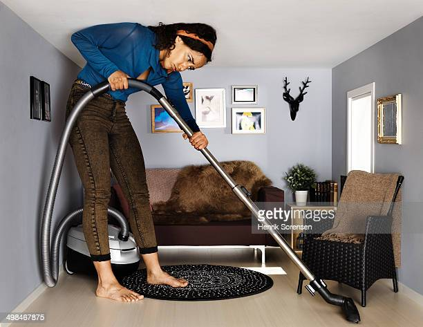 woman vacuum cleaning in smallscale living room - claustrofobia fotografías e imágenes de stock