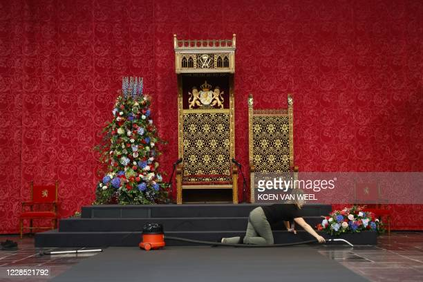 Woman vacuum cleanses the throne room on Prinsjesdag in the Grote Kerk prior to an official speech in The Hague on September 15, 2020. / Netherlands...