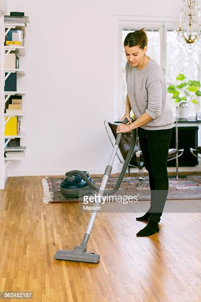 Woman vacuuming hardwood floor at home