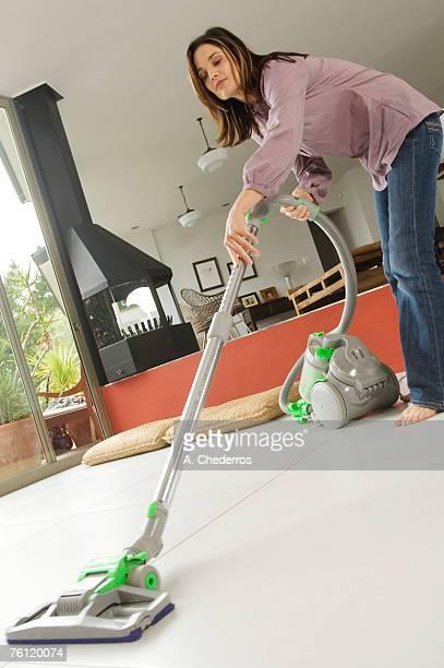 Woman vacuuming, indoors