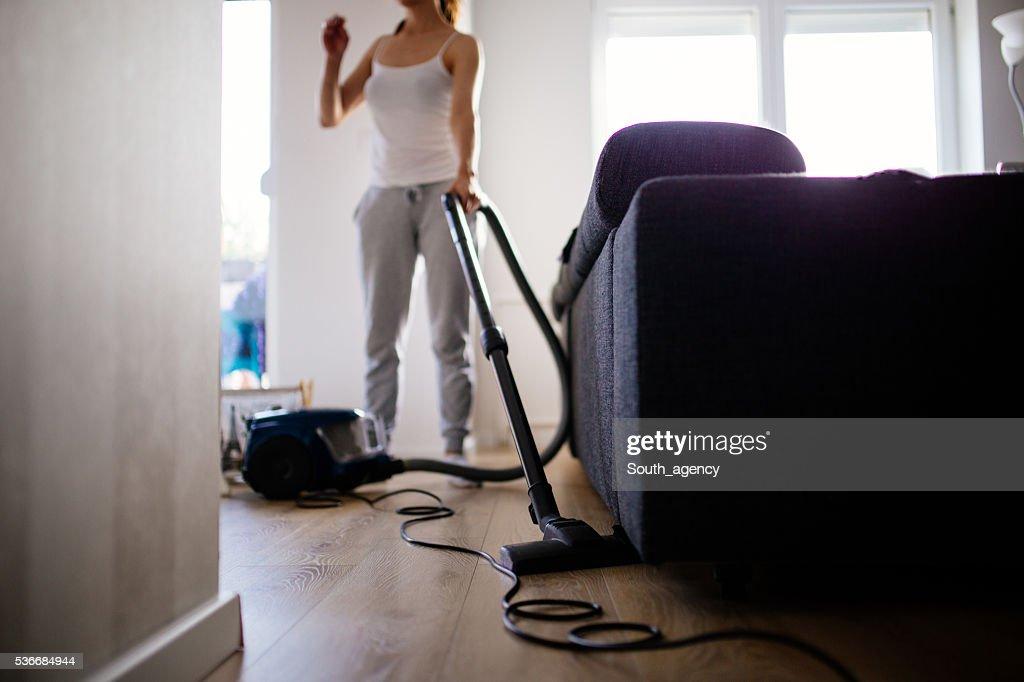 Woman vacuuming living room : Stock Photo