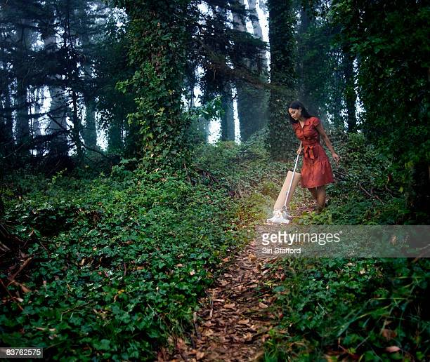 Woman vacuuming path in ivy covered forest
