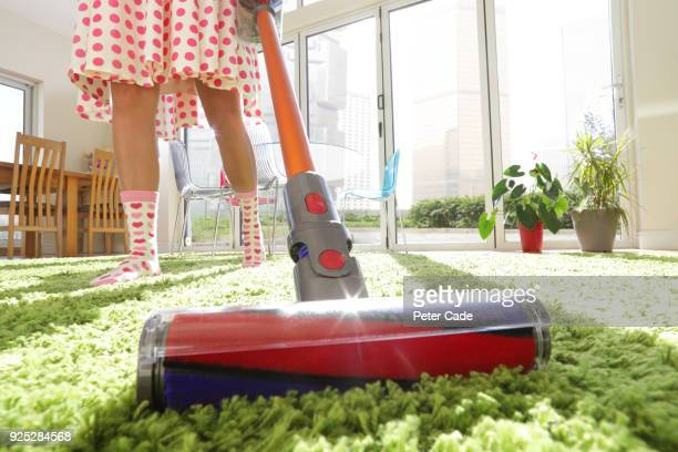 woman vacuuming rug - carpet stock pictures, royalty-free photos & images