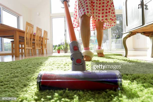 woman vacuuming rug - cleaner stock pictures, royalty-free photos & images