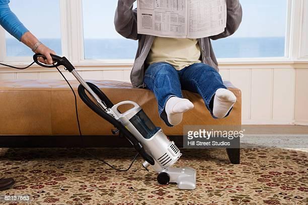 Woman vacuuming under man?s feet