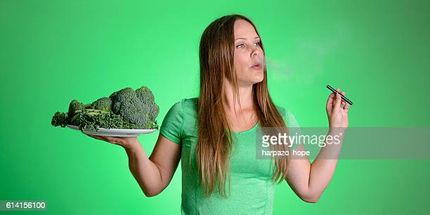 Woman vaping with a plate of vegetables.