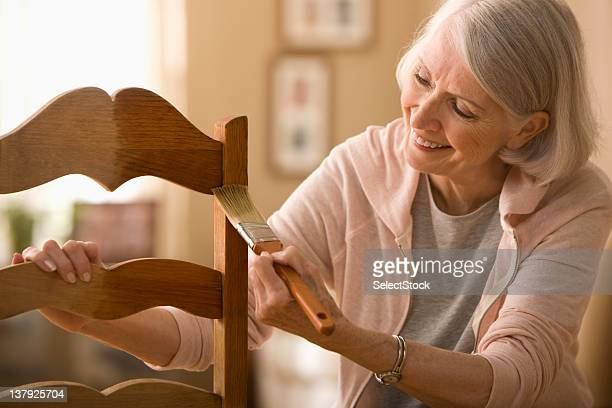 woman varnishing chair - independence stock pictures, royalty-free photos & images