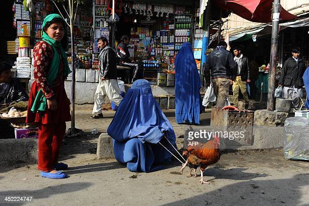 A woman vendor keeps a rooster tethered at the Bird Market in Kabul on November 27 2013 The wartorn country still faces poverty unemployment and lack...