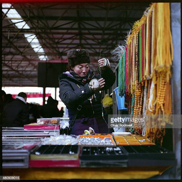 Woman vendor sells her wears of beaded necklaces in the famous Panjiayuan Market, Chaoyang District, Beijing, China