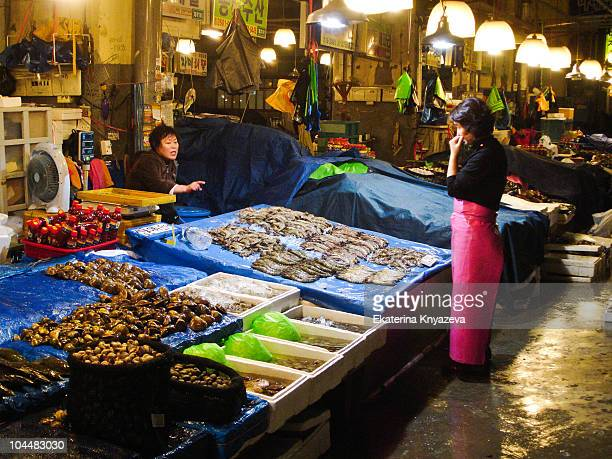 Woman vendor wearing a long rubber apron is standing in front of a seafood stall at Noryangjin Fish Market in Seoul, South Korea.