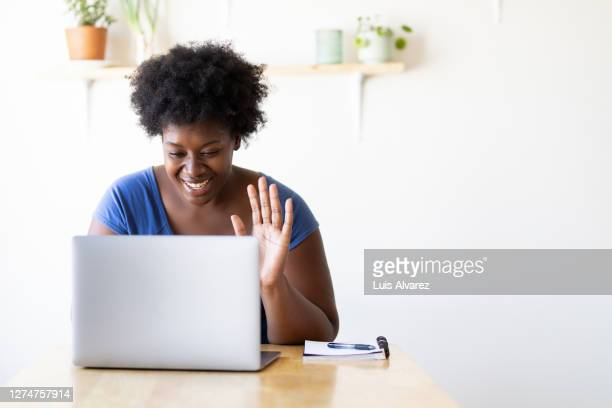 woman video calling using a laptop at home - looking at camera stock pictures, royalty-free photos & images