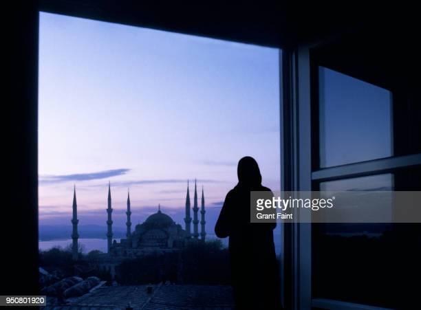 woman viewing blue mosque out window. - muslim praying stock pictures, royalty-free photos & images